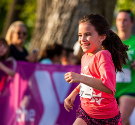 girl in pink shirt and shorts running while smiling