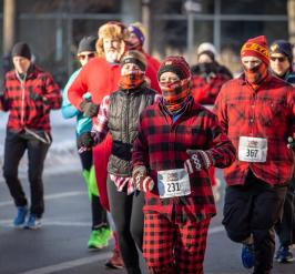 group of people decked out in flannel run in a street